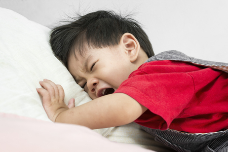 Photo pour Asia Baby Crying on the bed Put on a red shirt. - image libre de droit