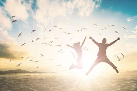 Foto de Silhouette of couple generation jump on beautiful background. - Imagen libre de derechos