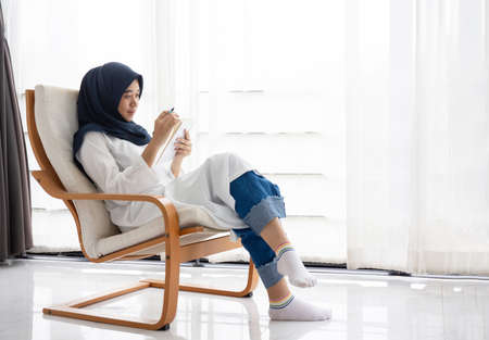 Foto de Young Muslim women Students is a creative freelance journalist sit writing to be entrepreneur job concept for hijab girl Islam religion Asian ethnic joyful internet banking on tablet mobile smartphone - Imagen libre de derechos