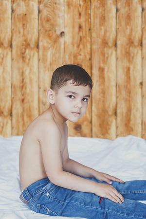 Photo pour Happy childhood concept. 6 years old boyhaving good time. Cute little kid sitting on comforter. Copy space - image libre de droit