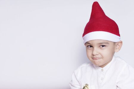 Photo for Portrait of a six-year-old middle eastern boy against the white background. Celebrating Christmas. 6-7 year old kid with Santa Claus hat. Copy space for text and ad - Royalty Free Image