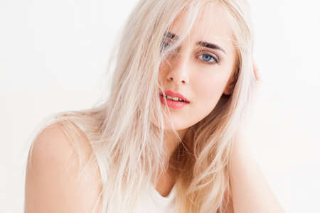Foto de confident blonde with big blue eyes, bright eyebrows. Her long white hair disheveled, she calmly and trustingly and looks into the camera. studio photo on white background. - Imagen libre de derechos