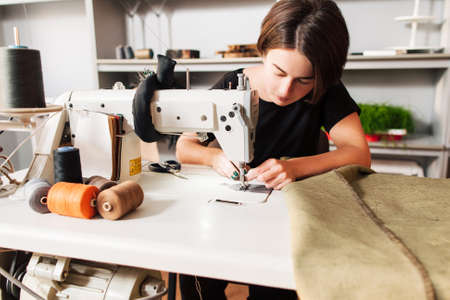 Foto de seamstress sews clothes and put thread in needle. Workplace of tailor - sewing machine, rolls of of thread, fabric, scissors. - Imagen libre de derechos