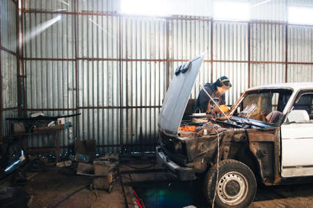 Foto de Service station for old damaged automobile. Bodywork and restore body and engine compartment. Workshop background - Imagen libre de derechos