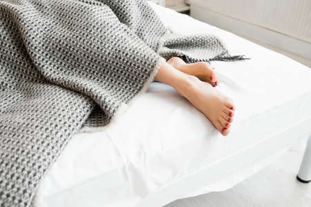 Photo pour Woman feet under gray blanket sideview. Beautiful young woman feet with red pedicure on the bed. Sleeping woman legs under the gray blanket - image libre de droit