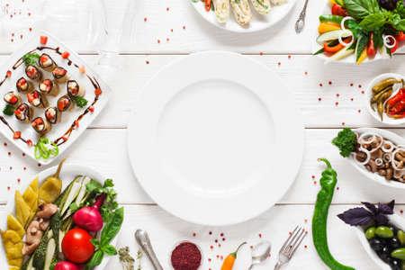 Foto de White ceramic plate surrounded by snacks, void. Variety of vegetarian meals make frame for empty dish. Cuisine, menu, food concept - Imagen libre de derechos