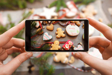 Photo pour Hands taking picture of gingerbread cookies. Close-up photo of smartphone photographing traditional Christmas treat assortment. Food photography concept - image libre de droit