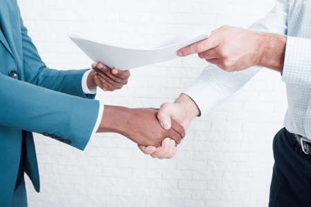 Foto de Handshake in office after making deal. Two owners of business signed contract about interracial cooperation. - Imagen libre de derechos