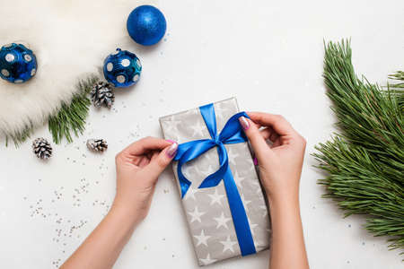 Foto de Festive background of Christmas present decoration. Unrecognizable woman wrapping gift box, ornament blue balls and pine branch laying on table nearby, top view with copy space. Handmade decor concept - Imagen libre de derechos