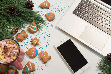Foto de Chatting during Christmas and New Year holidays. Festive background of laptop and smartphone near pine and cup of marshmallows with cookies, top view. Greetings in social network concept - Imagen libre de derechos