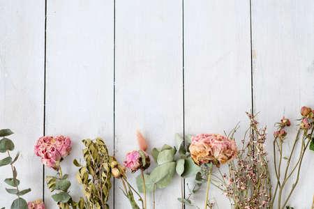 Foto de dried shabby chic flowers and twigs on white wooden background. free space concept - Imagen libre de derechos