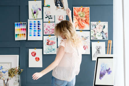 Photo pour creative art lifestyle. drawing hobby and self expression. painter dancing against the wall with her artwork. watercolor drawing assortment - image libre de droit