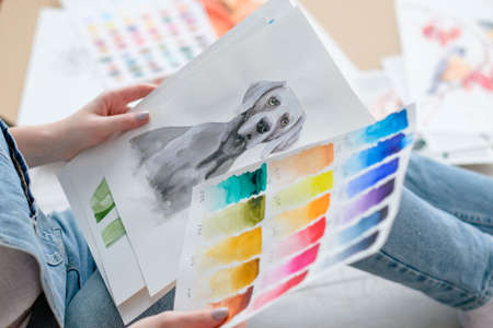 Photo pour creative art lifestyle. drawing hobby and self expression. woman looking at picture of a dog and color swatches - image libre de droit