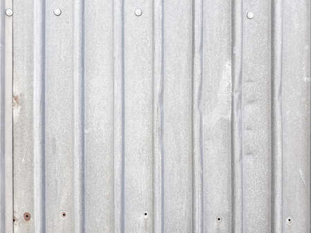 Foto de profiled metal sheet silvery background. industrial abstract design. vertical stripes. weathered dented surface with holes and rivets. copyspace concept - Imagen libre de derechos