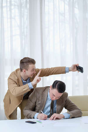 Photo for annoying intrusive coworker taking selfie with a busy colleague in office. business and work ethics - Royalty Free Image