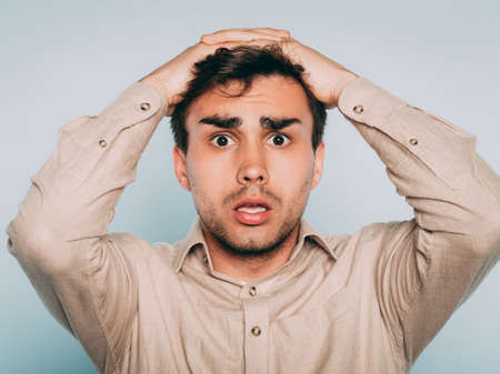 Photo pour oh no. terrified shocked desperate alarmed dismayed man clutching his head. portrait of a young brunet guy on light background. emotion facial expression. feelings and people reaction concept. - image libre de droit