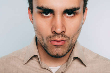 Foto de angry threatening and intimidating man. disrespect and arrogance. portrait of a young brunet guy on light background. emotion facial expression. feelings and people reaction concept. - Imagen libre de derechos