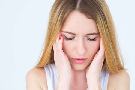 Photo pour emotion face. headache fatigue exhaustion. tired woman massaging her temples. young beautiful blond girl portrait on white background. - image libre de droit