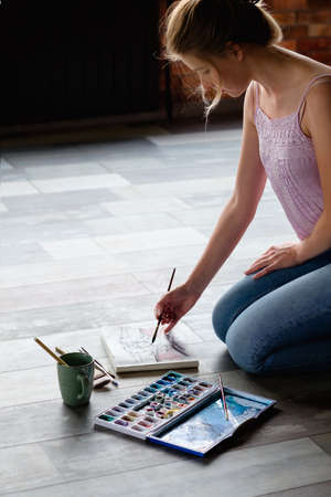 Photo pour creative leisure. painting hobby. artful personality. talented girl drawing a picture sitting on the floor. - image libre de droit