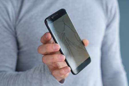 Foto de smashed shattered cracked screen. man holding damaged smart phone. mobile devices repair service concept. - Imagen libre de derechos