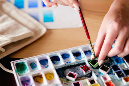 Foto per watercolor palette. artist tools instruments and inks for creative leisure. painting lessons concept. woman loading brush with color. - Immagine Royalty Free