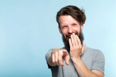 Foto de omg. ha-ha. bearded hipster man mocking and laughing at viewer pointing finger and covering mouth. sneer humiliation and psycological abuse concept. portrait of a grinning guy on blue background. - Imagen libre de derechos