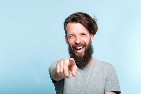 Foto de young bearded hipster man mocking and laughing at viewer pointing finger. mockery sneer jeer concept. portrait of a grinning guy on blue background. - Imagen libre de derechos
