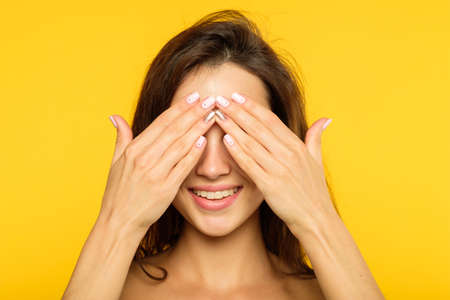 Photo for hide and seek. facial expression. emotional portrait. smiling joyful jolly woman covering eyes with hands. young beautiful brown haired girl on yellow background. - Royalty Free Image