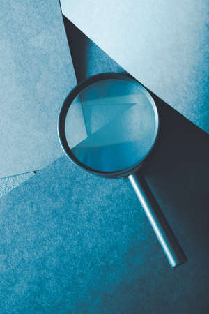 Foto de magnifying glass. science research exploration and scrutiny concept. loupe on layered blue paper background. - Imagen libre de derechos