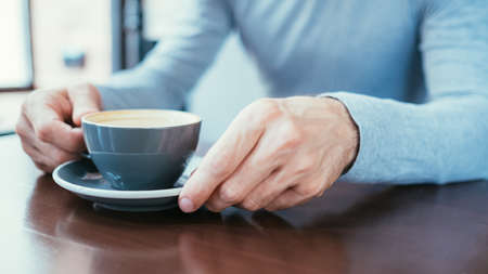 Foto per man hands holding a mug of coffee. caffeine addiction and bad habits. - Immagine Royalty Free