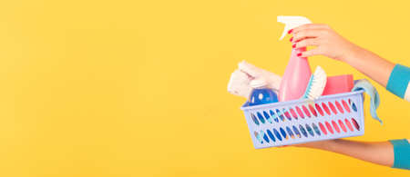 Foto de Cleaning concept. DIY home cleanup. Woman with basket of supplies pointing atomizer. Copy space on yellow background. - Imagen libre de derechos