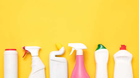 Foto de House cleaning supplies on yellow background. Row of plastic bottles with copy space. - Imagen libre de derechos