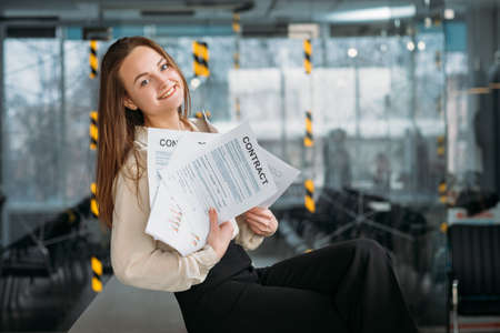 Photo for Corporate lawyer at workplace. Smiling young woman sitting on desk with handful of contracts. - Royalty Free Image