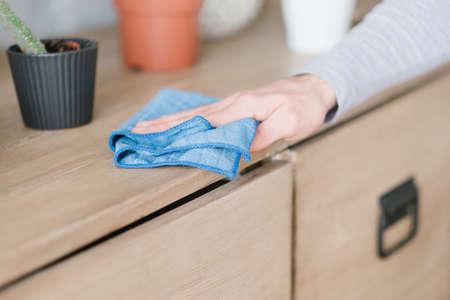 Foto de Cleaning concept. Morning household chores. Mans hand dusting dresser. - Imagen libre de derechos