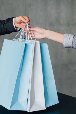 Photo pour Online shopping. Delivery service. Man handing over paper bags to woman. Cropped shot. - image libre de droit