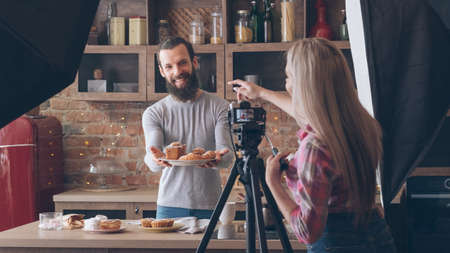 Photo for Homemade cooking. Baking hobby. Backstage photography. Woman shooting smiling man with fresh cakes and pastries. - Royalty Free Image