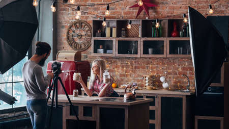 Photo for Vlog on healthy nutrition. Loft kitchen studio. Backstage photography. Couple shooting video tutorial. - Royalty Free Image