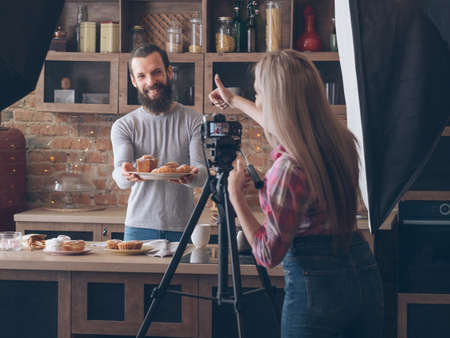 Photo for Food photographer at work. Backstage photography. Woman thumb up shooting smiling man with fresh pastries assortment. - Royalty Free Image