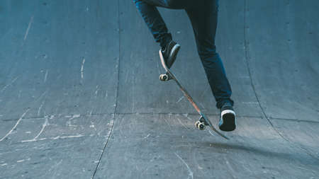 Foto de Skateboarding hobby. Man active life. Guy on skateboard performing ollie trick on ramp. Copy space. - Imagen libre de derechos