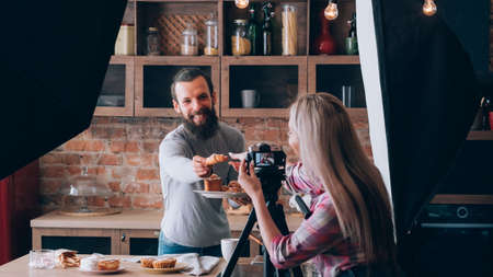 Photo for Woman shooting food blogger. Photo session. Man at kitchen counter with plate of fresh pastries. Have a treat. Backstage photography. - Royalty Free Image