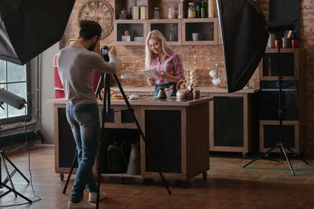 Photo for Man shooting food blogger. Photo session. Woman at kitchen counter with tablet. Backstage photography. - Royalty Free Image