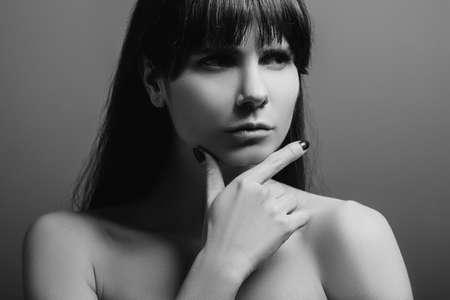 Foto de Doubtful looking pretty lady. Concentrated facial expression. Black and white closeup portrait of emotional young woman. - Imagen libre de derechos