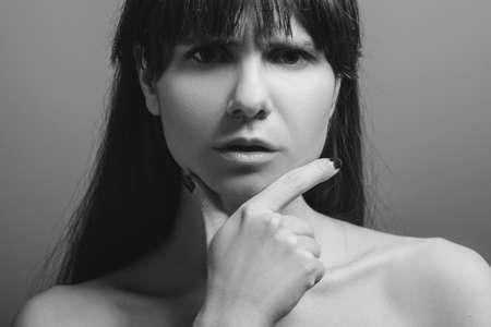 Foto de Confused pretty lady. Pensive facial expression. Black and white closeup portrait of emotional woman with bare shoulders. - Imagen libre de derechos