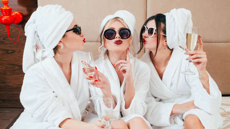 Foto de Celebration party at spa. Friends congratulation. Young women with champagne. Sunglasses, bathrobes and turbans on. - Imagen libre de derechos