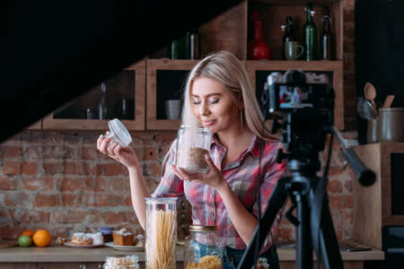 Photo for Vlog episode on nutrition. Cooking. Loft kitchen studio. Backstage photography. Blonde young woman with jars. - Royalty Free Image