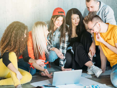 Photo for Millennials business life. Young team sitting on floor, discussing project improvement, brainstorming, looking for solution. - Royalty Free Image