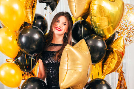 Photo for Special day. Portrait of brunette lady standing with bunch of golden and black balloons. Happy facial expression. - Royalty Free Image