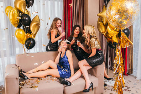 Photo for Girls party in luxury room decorated with golden balloons and confetti. Ladies sitting on sofa, chatting, smiling, having fun. - Royalty Free Image