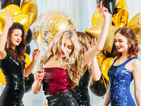 Photo for Fancy party. Festive event. Pretty girls dancing in sparkling dresses, enjoying celebration at home decorated with balloons. - Royalty Free Image