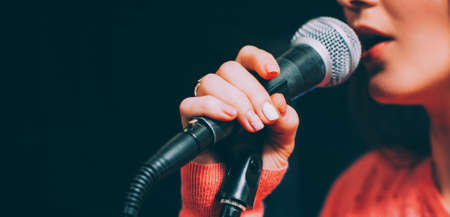 Photo for Singer at microphone. Woman singing and holding mic. Female vocal talent. Music show recital. - Royalty Free Image